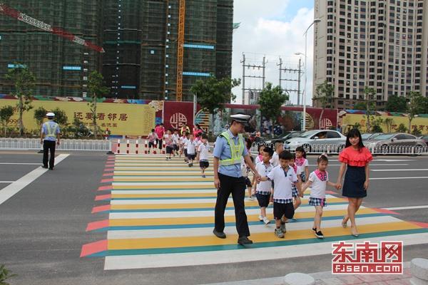 幼儿园的小朋友在民警和老师的带领下,踩着彩色立体斑马线穿过马路