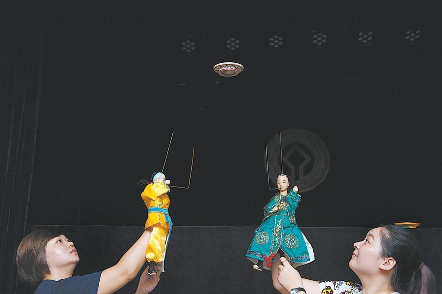 两位演员在练习木偶抛接飞盘,在掌中木偶的戏份中唱念做打的成分一点都没有少。 东南网11月5日讯(福建日报记者 王毅 通讯员 姚煜娟 图/文)有着千年历史的掌中木偶,又称布袋木偶是闽南艺术的瑰宝,传神逼真的人物形象全靠演员手掌与五指的变化去体现。如今,拿捏这种传统艺术的大都是二三十岁的年轻人。 掌中木偶在舞台上表演,只见木偶活灵活现,不见演员在幕后台下的苦心操作。这样的表演形式对于很多喜欢张扬个性,展现自我的年轻人来说,实在是憋屈。只有真心爱木偶的人,才会甘于在幕后对镜苦练,在台上以巧手游戏偶身,让观众